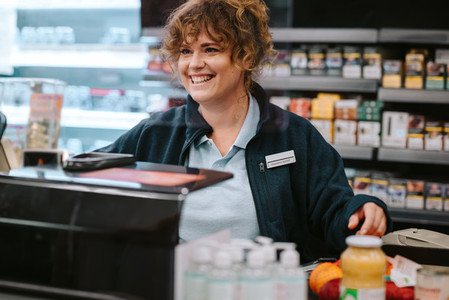 Cashier working at supermarket checkout