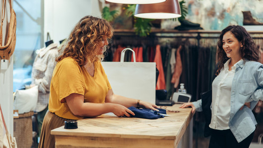 Shop clerk assisting customer at clothing store checkout