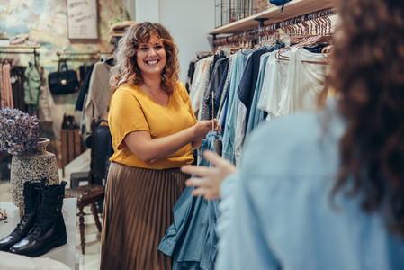 Clothing store owner assisting customer in her store