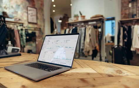 Laptop on checkout counter of clothing store