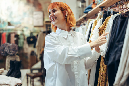 Attractive woman choosing clothes in store