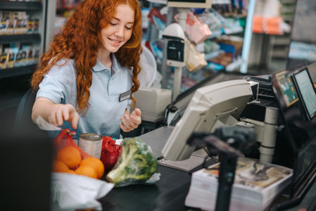 Young female working at billing counter in grocery store