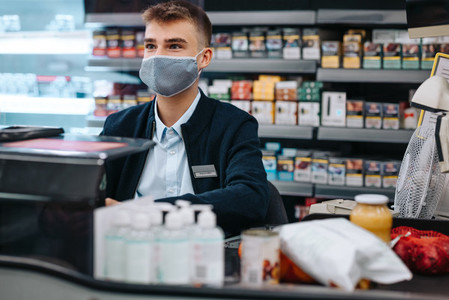 Man working in supermarket with a face mask