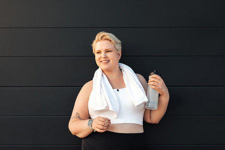 Smiling plus size woman sportswear standing at black wall Healthy woman relaxing after training