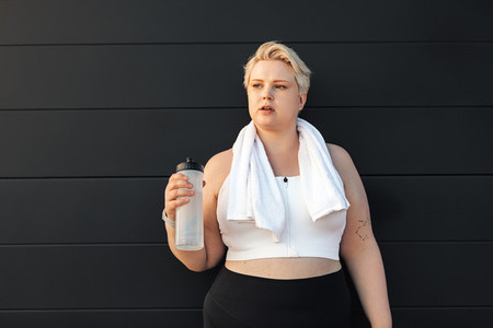 Portrait of a tired curvy woman standing at wall with a towel