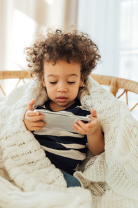 Little boy covered in blanket watching content on a smartphone