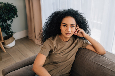 Portrait of a beautiful woman with black curly hair sitting on couch