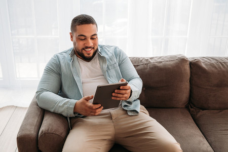 Smiling man with digital tablet sitting on a sofa