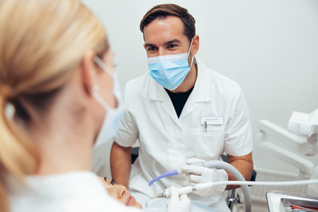Dentist discussing with assistant during a treatment