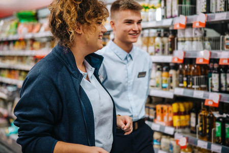 Woman with new employee in supermarket