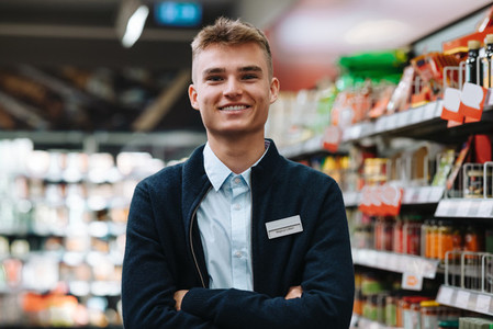 Confident young supermarket worker