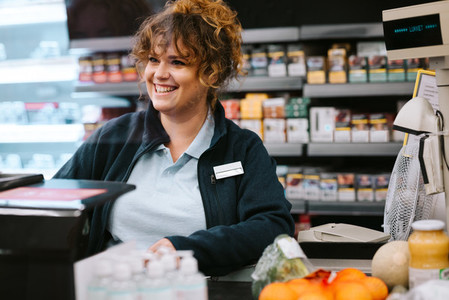 Supermarket cashier attending customer