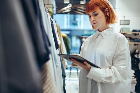 Female entrepreneur using digital tablet in her clothing store