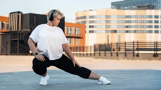Plus size woman stretching leg