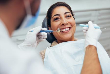 Woman having teeth examined at dentist