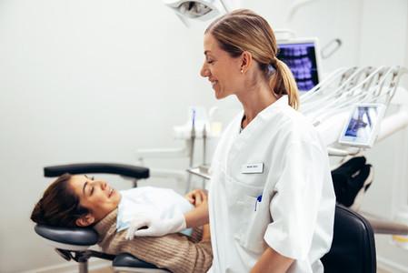 Dentist preparing female patient for treatment