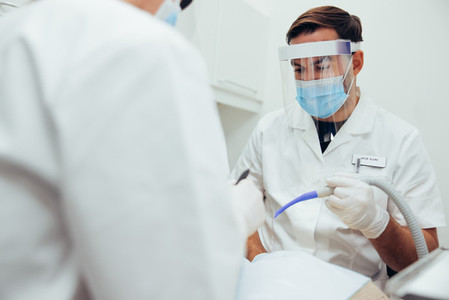 Dental doctor treating patient in his dentistry