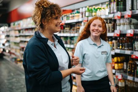Supermarket manager training young woman worker