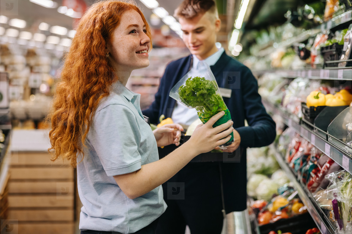 Young workers packing fresh produce on the shelves