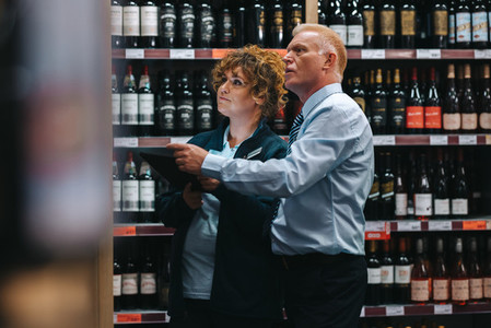Sommeliers taking inventory in liquor store