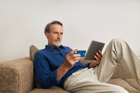 Mature man doing online payment from digital tablet