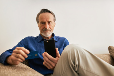 Senior man paying online  Male in casual clothes sitting on sofa holding a credit card