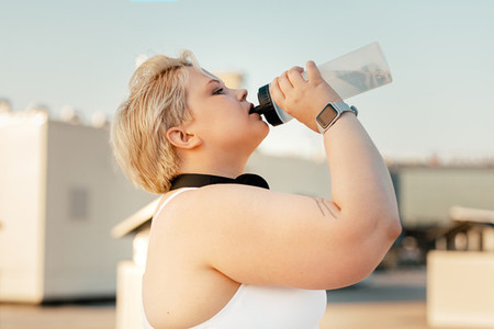 Side view of plus size woman taking a break during training