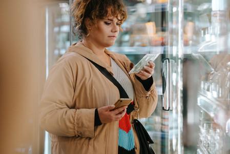 Customer reading product information at supermarket