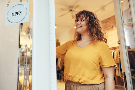 Fashion boutique owner putting OPEN sign on door