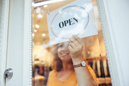 Woman hanging Open sign on her store door