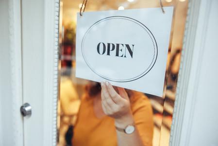 Woman hanging OPEN sign on store door