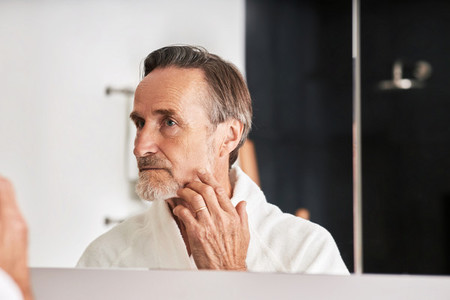 Senior man touching his face