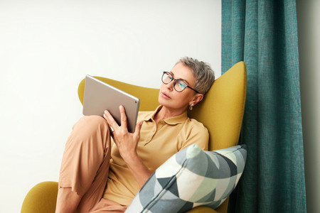 Mature woman sitting on armchair
