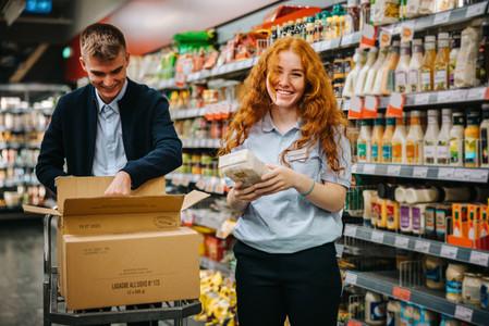 Supermarket store assistants restocking the shelves