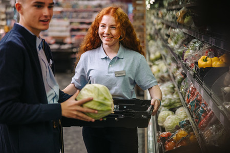 Shop assistants re stocking fresh vegetables in produce aisle
