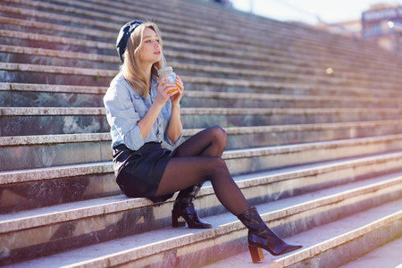Blonde woman with beret  drinking a natural orange juice in a crystal glass  sitting on some steps