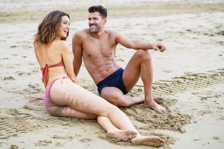 Young couple sitting together on the sand of the beach
