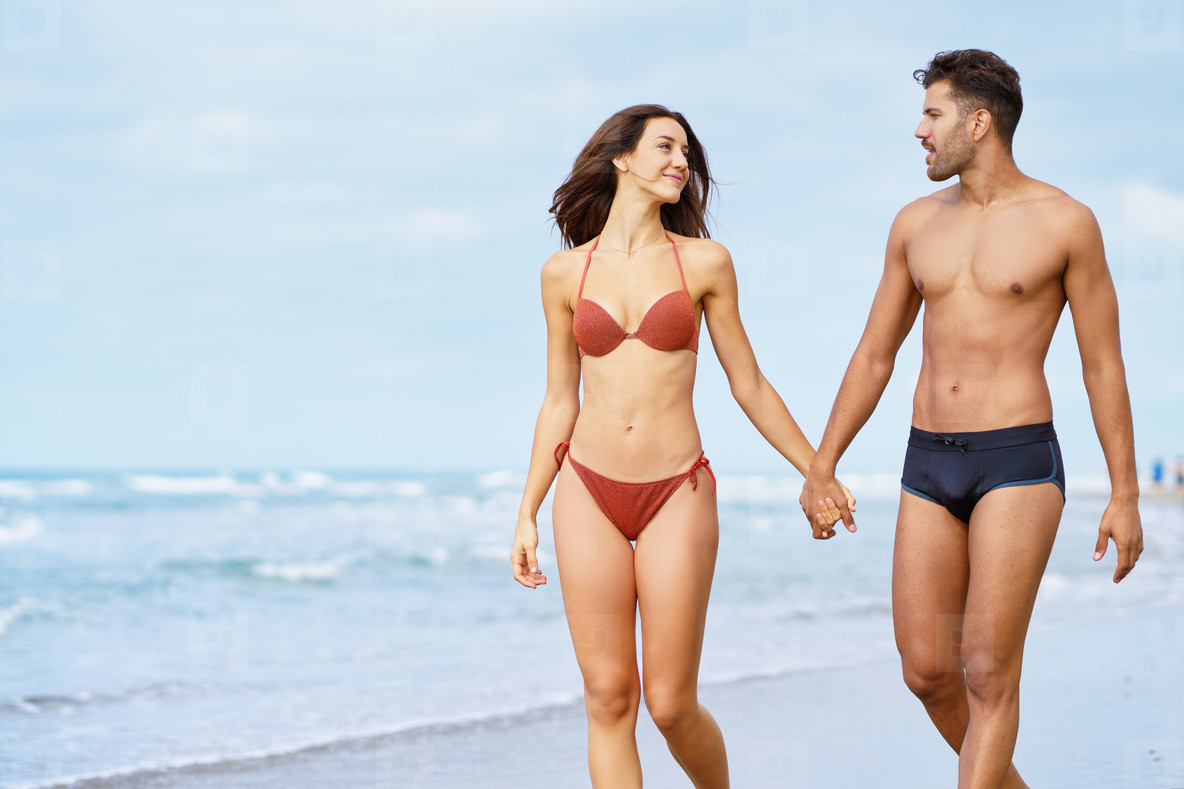 Young couple of beautiful athletic bodies walking together hand by hand on the beach