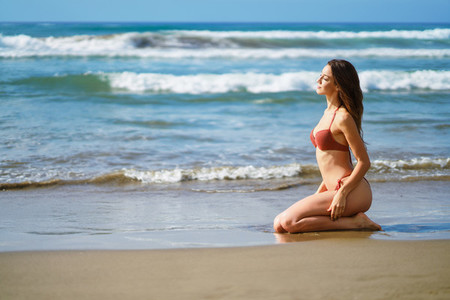 Woman with beautiful body on her knees on the sand of the beach