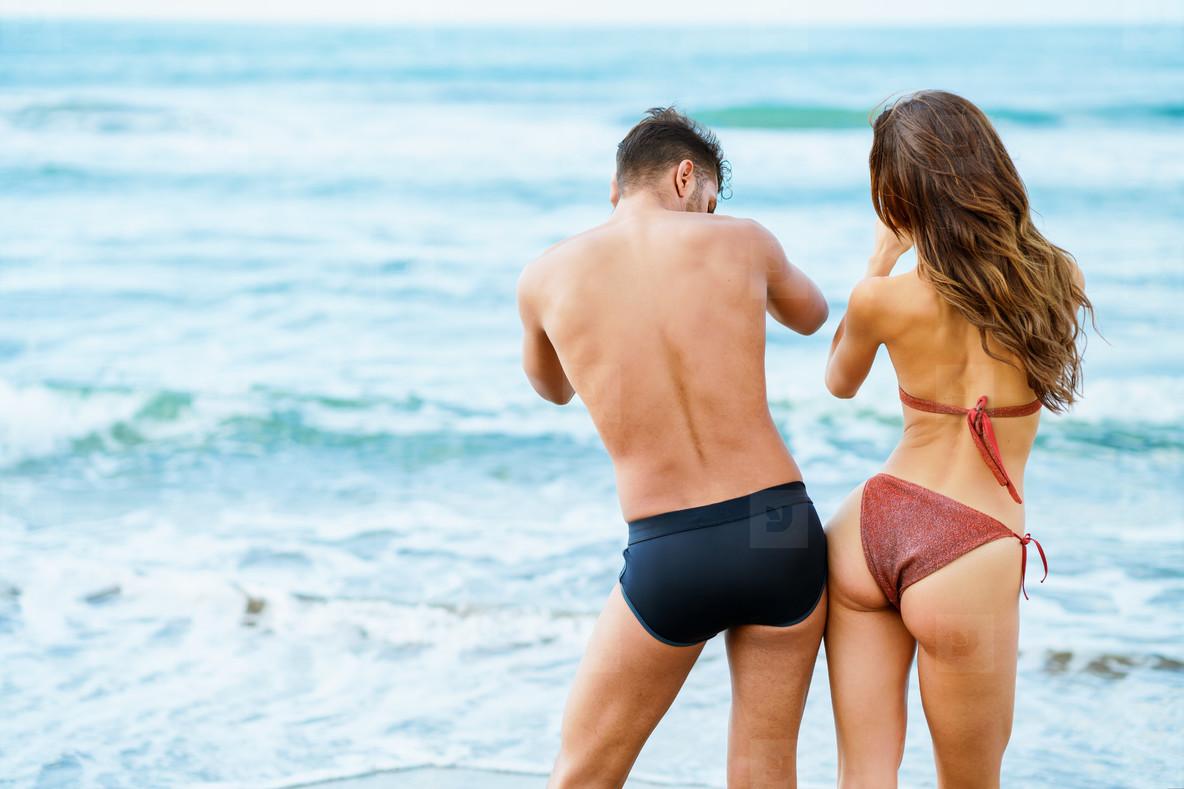 Young couple with beautiful bodies in swimwear having fun on a tropical beach
