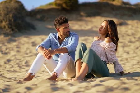 Attractive couple sitting on the sand of the beach