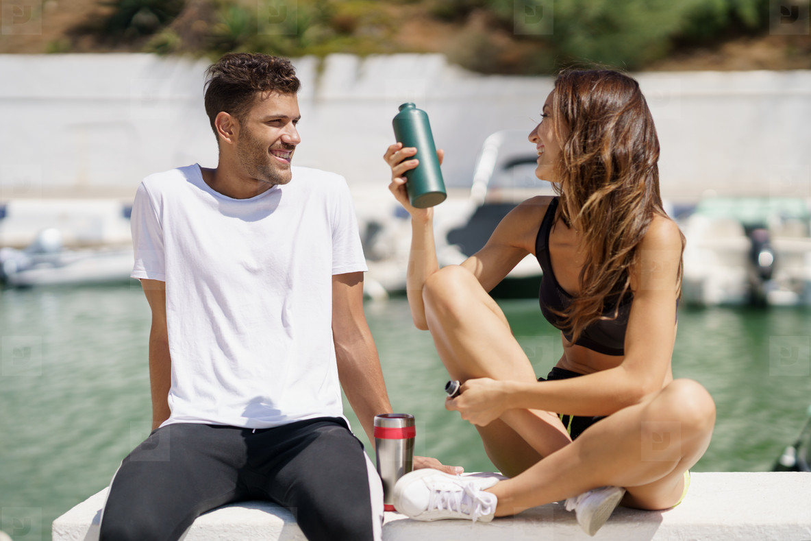 Young sporting couple hydrate themselves with water in metal cans while taking a break after sport