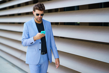 Man walking down the street using his smartphone with a serious expression