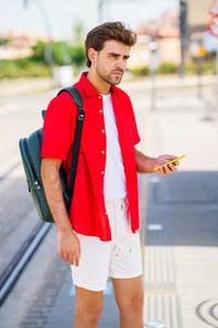 Young man waiting for a train at an outside station