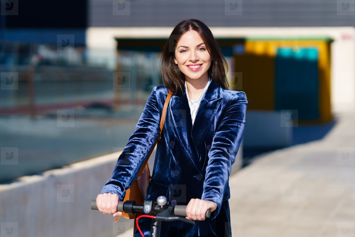 Young business woman wearing blue suit using electric scooter