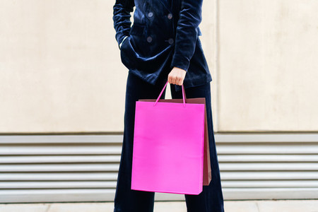 Unrecognizable woman with shopping bags in urban background