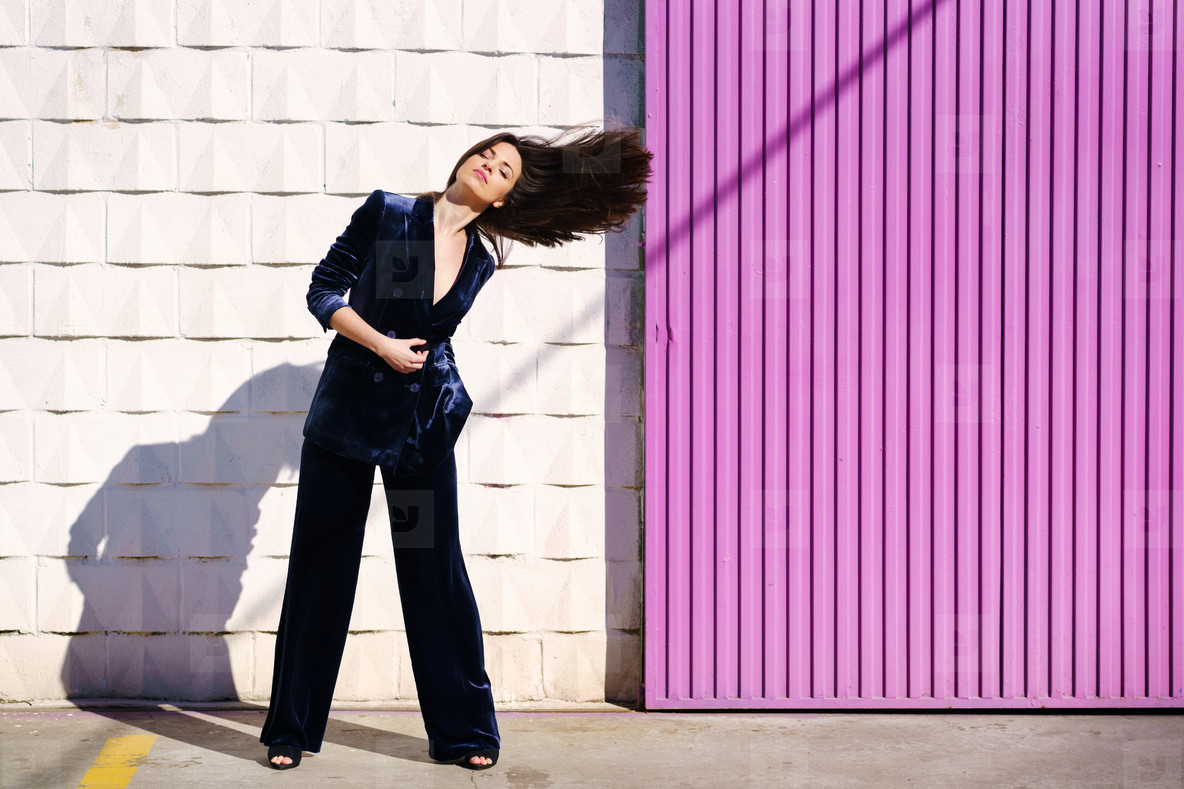 Woman wearing blue suit posing near pink shutter  moving her hair