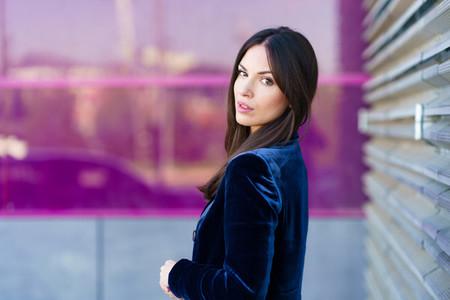 Woman wearing blue suit posing near a modern building