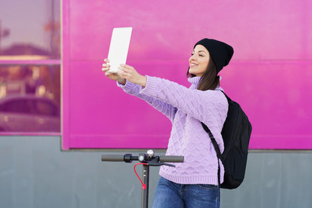 Woman in her twenties with electric scooter taking a selfie with a digital tablet outdoors