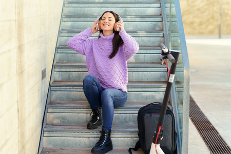 Young woman with electric scooter  listening to music with wireless headphones